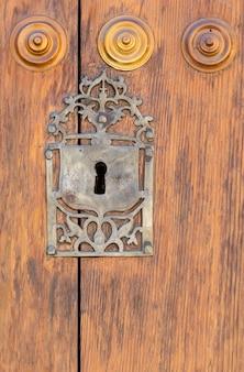 Buraco da fechadura em uma porta de madeira apainelada velha; enferrujado e intemperizado