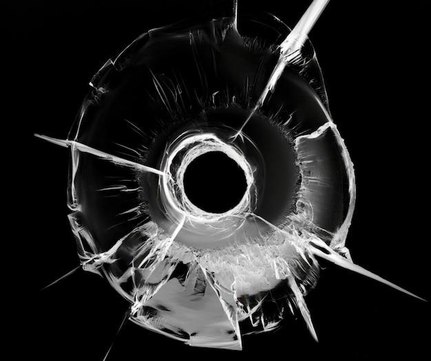 Buraco de bala no vidro no preto. textura de vidro rachado.