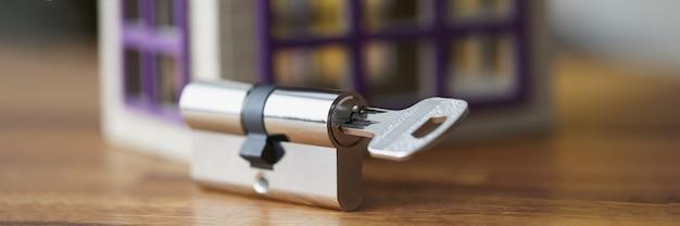 Buraco de fechadura com a chave perto de uma casa de brinquedo de madeira.