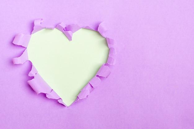 Buraco de forma de coração azul através de papel roxo