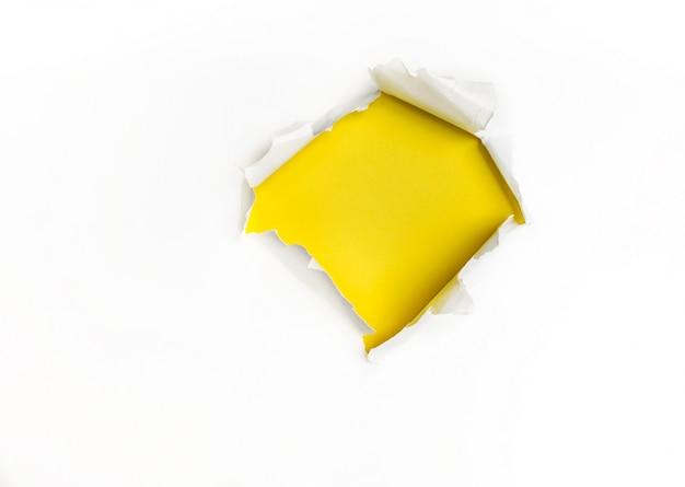 Buraco em papel branco com uma parede amarela