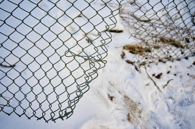Buraco na cerca de arame para escapar da prisão ou instituição fechada para pacientes com doenças mentais no inverno nevado.