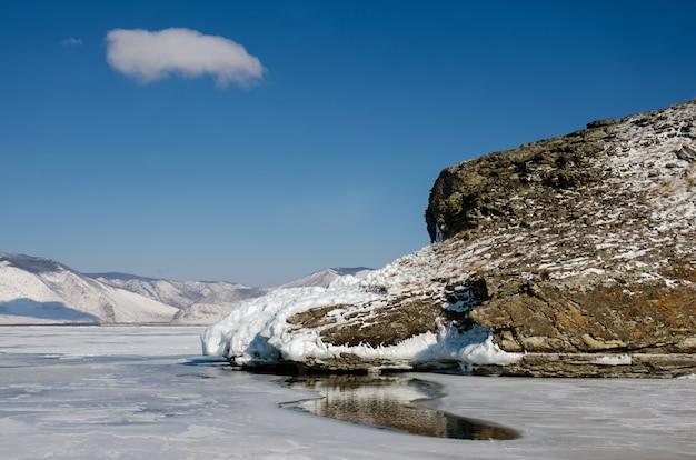 Buraco no gelo do lago baikal com mais de um metro de espessura perto da rocha