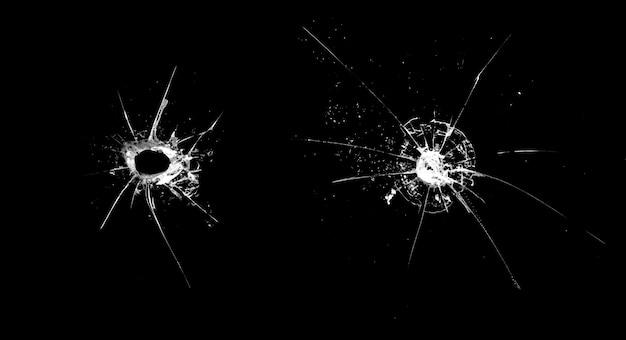 Buraco no vidro com rachaduras isoladas em um fundo preto
