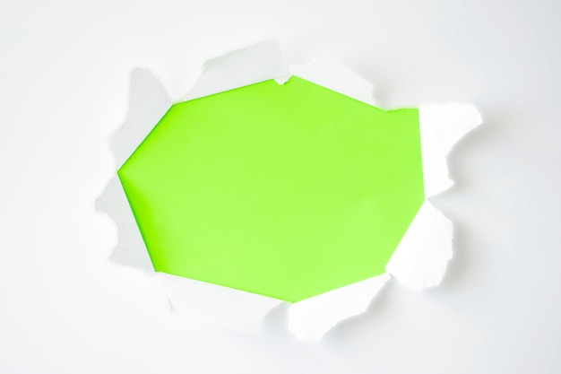 Buraco oval rasgado em papel branco com bordas rasgadas e fundo verde. copie o espaço, a textura do papel.