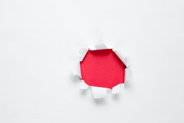 Buraco rasgado com espaço vermelho para texto em um fundo de papel branco