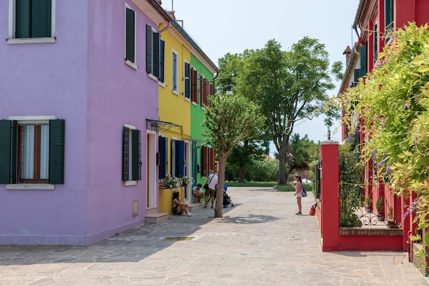Burano, veneza, itália - 2 de julho de 2018: vista panorâmica de casas coloridas de burano é uma ilha na lagoa veneziana. as pessoas caminham e descansam nas ruas. dia ensolarado de verão e céu azul