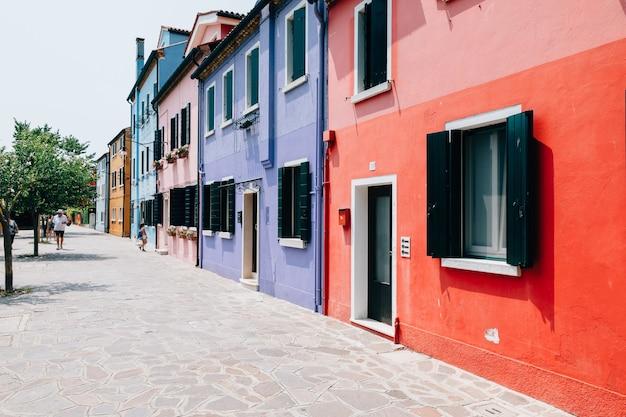 Burano, veneza, itália - 2 de julho de 2018: vista panorâmica de casas coloridas de burano é uma ilha na lagoa veneziana. as pessoas caminham e descansam nas ruas. dia ensolarado de verão e céu azul Foto Premium