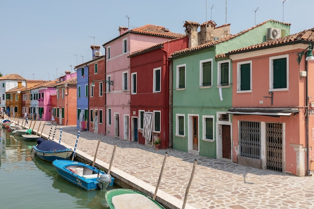 Burano, veneza, itália - 2 de julho de 2018: vista panorâmica de casas coloridas e canal de água com barcos em burano, é uma ilha na lagoa veneziana. pessoas caminham e descansam nas ruas