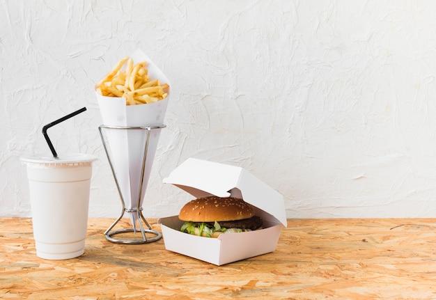 Burger; batatas fritas e copo de eliminação no tampo da mesa de madeira