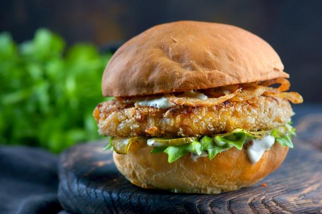 Burger de peixe com cebola frita e molho