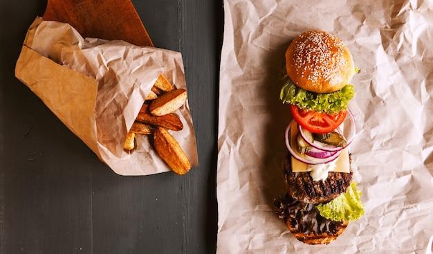Burger se decompôs em seus componentes em papel kraft em uma mesa de madeira. pacote de batatas fritas.