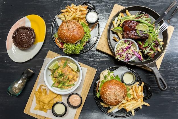 Burgersm batatas fritas, ceviche, costelas e muffin em uma mesa de madeira