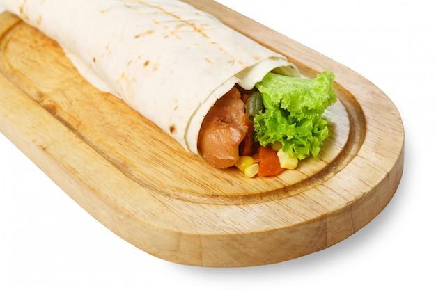 Burrito com frango e legumes na mesa de madeira