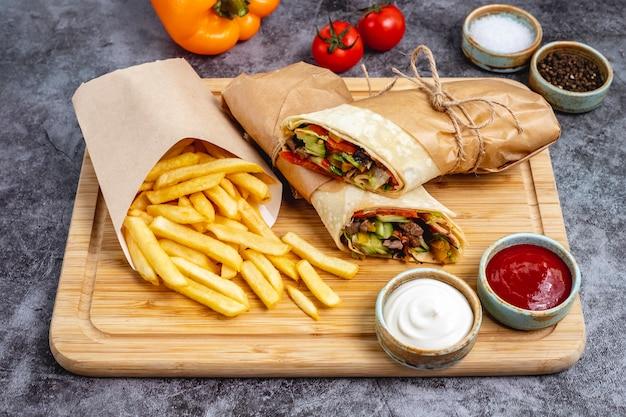 Burrito de carne com jalapeno de alface pepino tomate servido com batatas fritas e molhos horizontais