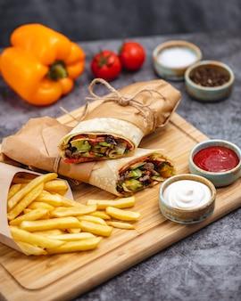 Burrito de carne com jalapeno de alface pepino tomate servido com batatas fritas e molhos verticais