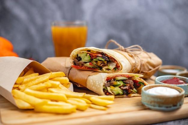 Burrito de carne com jalapeno de alface pepino tomate servido com batatas fritas e molhos