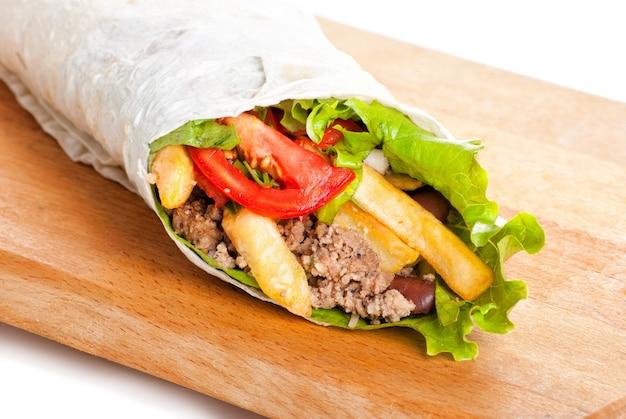 Burrito de carne com pimentão amarelo e vermelho, batata frita e tomate no prato