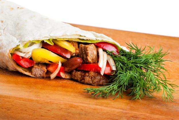 Burrito de carne com pimentão amarelo e vermelho, cebola e tomate no prato