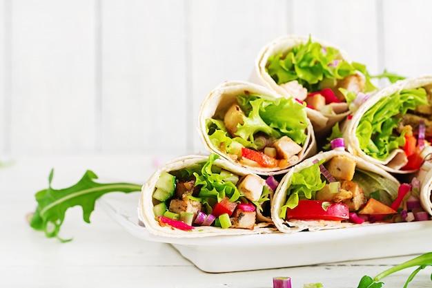 Burrito de galinha. almoço saudável. tortilha de fajita de comida de rua mexicana envolve filé de frango grelhado e legumes frescos.