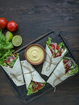 Burrito embrulhado com frango e legumes close-up sobre uma mesa de madeira.