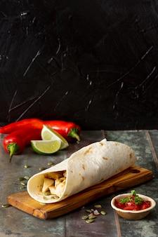 Burrito na tábua de cortar perto de pimentas, limão e molho de tomate