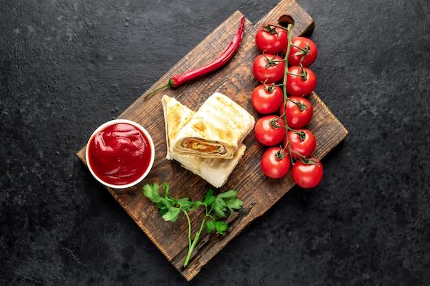 Burrito rolando com presunto e queijo em uma mesa de concreto
