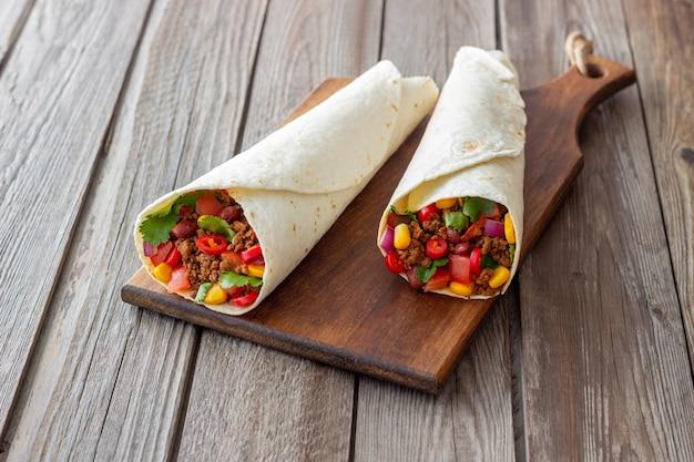 Burritos com carne, feijão, milho, tomate, cebola e pimenta. comida mexicana. receita.