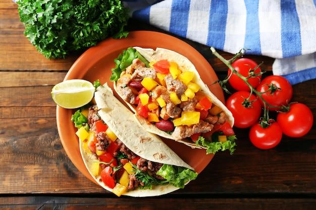 Burritos de carne caseiros com legumes no prato, mesa de madeira