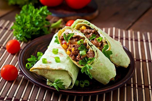 Burritos envolve com carne picada e legumes em um fundo de madeira