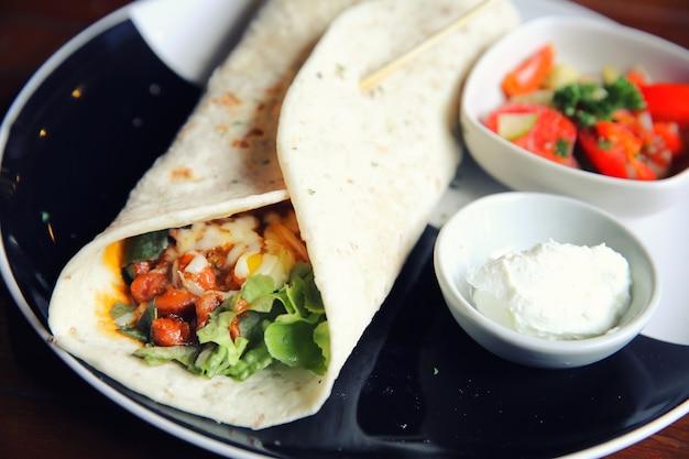 Burritos mexicanos em um prato com salada de tomate