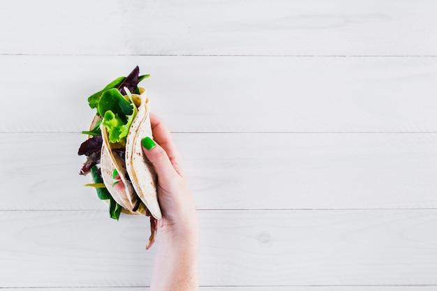 Burritos mexicanos saborosos com a mão