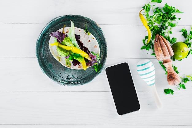 Burritos mexicanos saborosos com smartphone