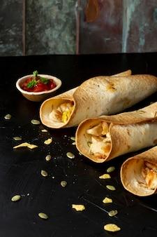 Burritos saborosos com frango e molho na tigela