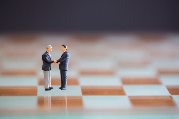 Buseinessman aperta as mãos para bons negócios coorporativos com o conceito de jogo de xadrez.