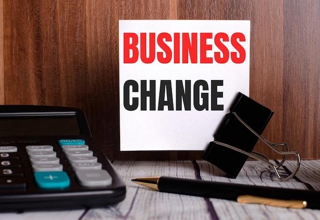Business change está escrito em um cartão branco em uma superfície de madeira ao lado de uma calculadora e caneta