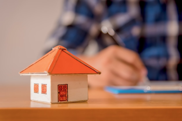 Business real estate concept, modelo de casa em madeira e fundo desfocado.