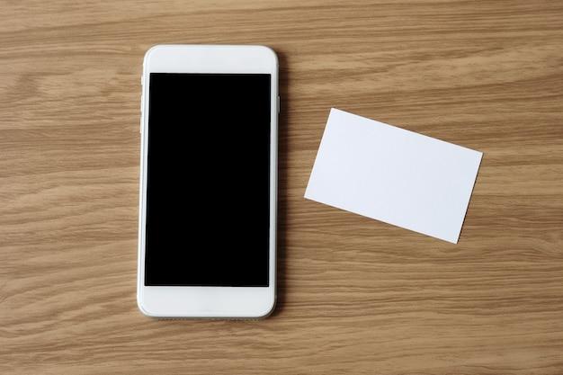 Businesscard branco em branco e smertphone com fundo de tela do dispositivo em branco