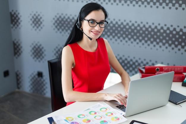 Businesslady atraente jovem de vestido vermelho e óculos sentar à mesa e trabalhar com o laptop
