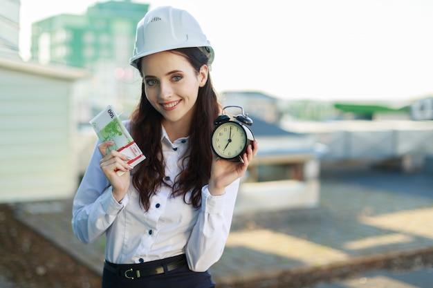 Businesslady atraente na blusa branca, capacete e saia preta fica no telhado e segura dinheiro e despertador