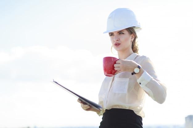 Businesslady atraente na blusa branca, relógio, capacete e saia preta ficar no telhado