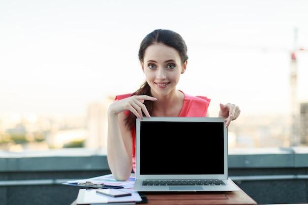 Businesslady atraente na blusa rosa sentar no telhado e trabalhar com laptop, mostrar laptop vazio
