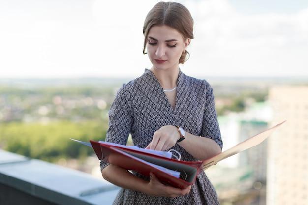 Businesslady atraente vestido estampado ficar no telhado e segurar a pasta de papel