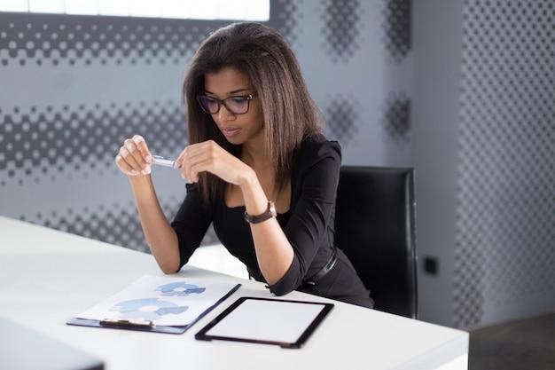 Businesslady jovem atraente na suíte forte preto sentar à mesa do escritório