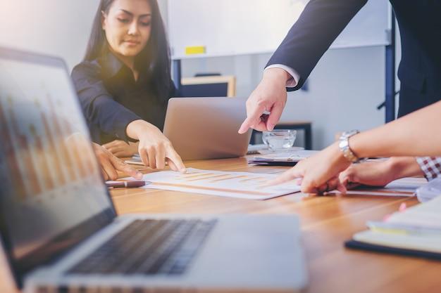 Businesspeoples reunião apontando para gráfico no relatório de negócios na mesa