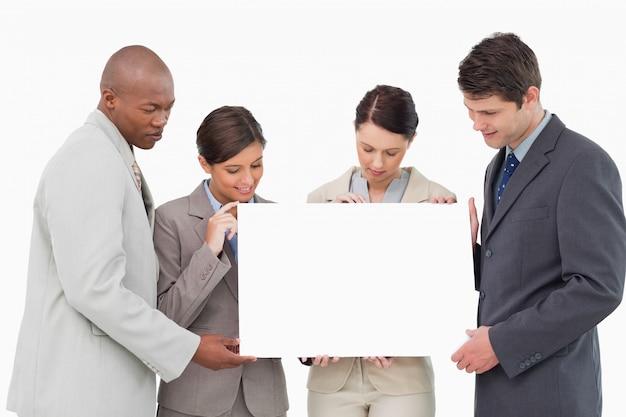 Businessteam segurando sinal em branco juntos