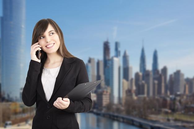 Businesswoma conversando com dispositivos móveis em ambiente urbano