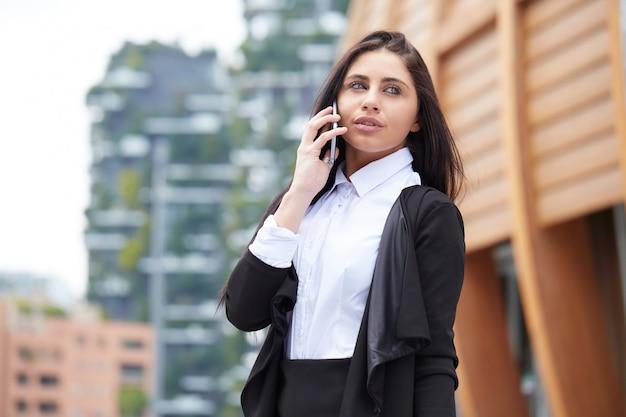 Businesswoma falando ao celular em ambiente urbano