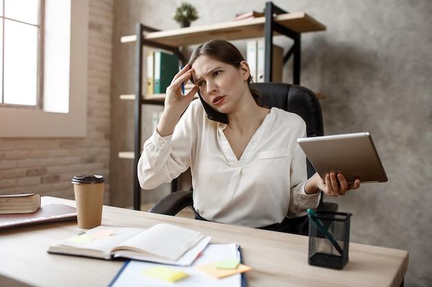 Busineswoman jovem tem conversa difícil no telefone. ela se senta à mesa na sala. modelo espera tablet.