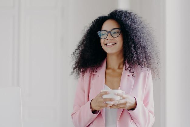 Busineswoman próspero afro-americano bonito espera parceiro no escritório, bebe café